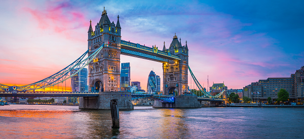 Dramatic sunset skies above the iconic span of Tower Bridge framing the futuristic skyscrapers of the Square Mile financial district above the slow moving waters of the River Thames in the heart of London, Britain's vibrant capital city.