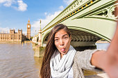 London travel selfie tourist woman making silly faces. Funny Asian girl sticking out tongue doing cheeky face for mobile phone app picture at Westminster bridge, Big Ben, UK.
