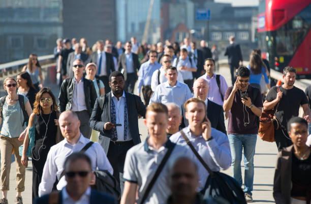 london, uk. verschwommenes bild von büroangestellten, überqueren die london bridge in den frühen morgenstunden auf dem weg in die city of london. - große personengruppe stock-fotos und bilder