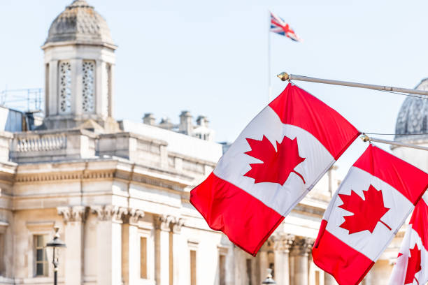 London, UK High Commission of Canada with closeup of row of red Canadian flags on Cockspur Street in Westminster stock photo