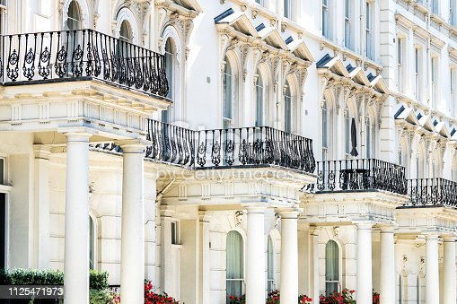 London, UK Street road Chelsea Kensington with terraced housing balconies buildings and columns in old vintage historic traditional style flats