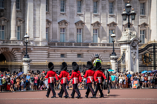 London, England - August 2021: Panoramic view of mounted soliders of the cavalary in ceremonial dress past Buckingham Palace after the Changing of the Guard ceremony