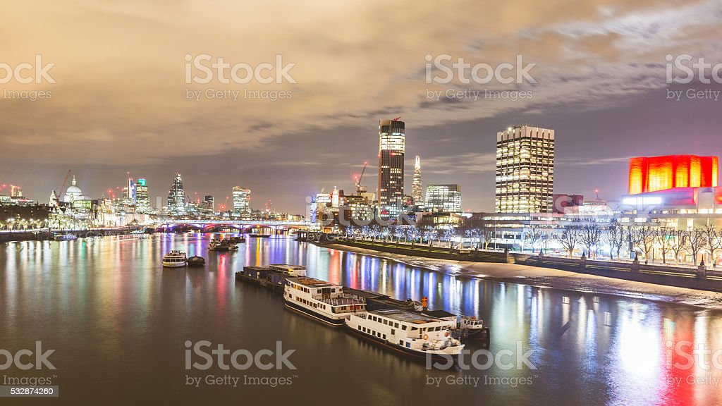 London view at night with boats and skyscrapers stock photo