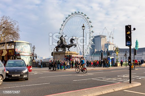 London, United Kingdom - Feb 21, 2018: London view with tourists walk near Boadicea and Her Daughters bronze sculptural group and London Eye giant Ferris wheel on a background