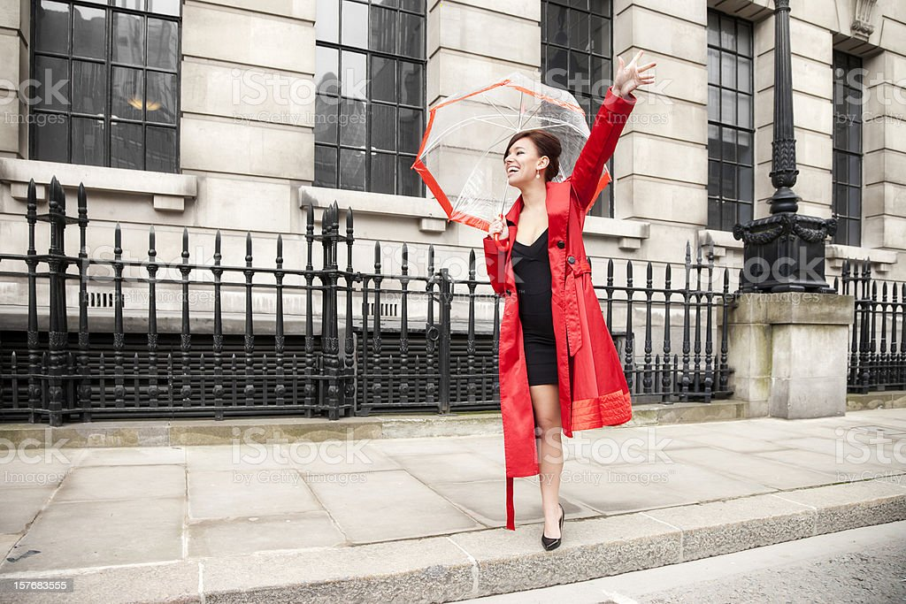 London Woman in Red Hailing a Taxi Cab stock photo