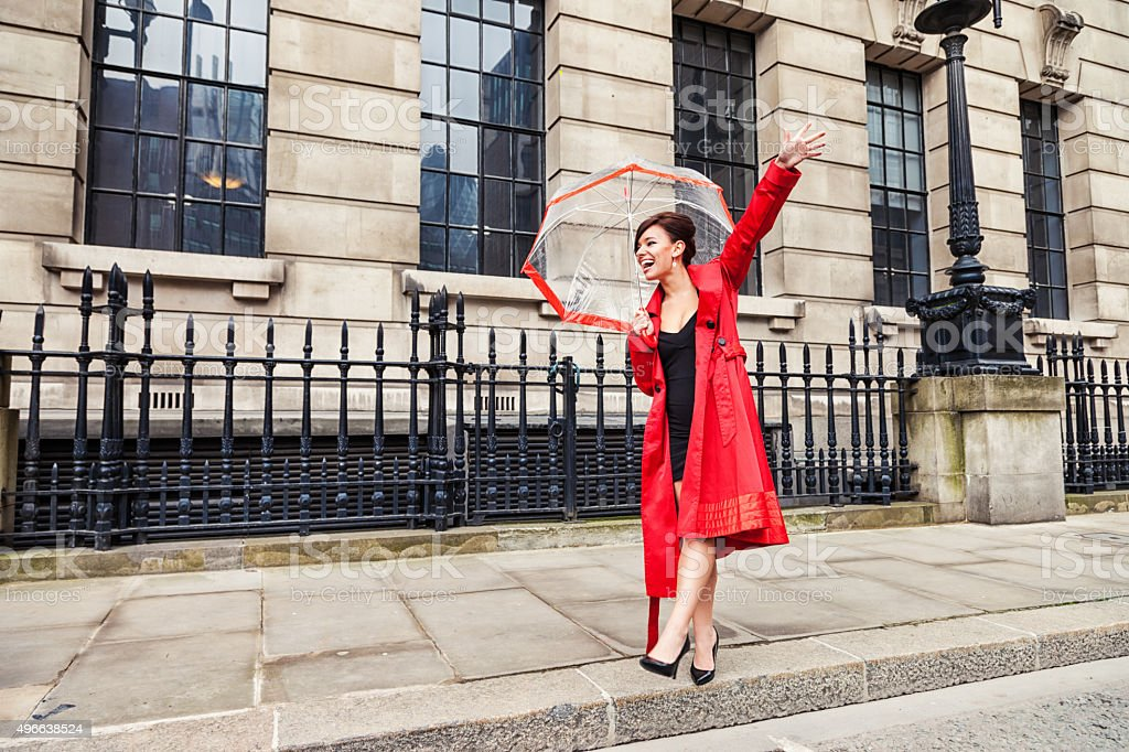 London mulher em vermelho chamar um táxi - foto de acervo