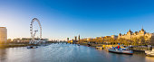 London's skyline view at sunrise with famous landmarks, Big Ben, Houses of Parliament and ships on River Thames with clear blue sky - London, UK