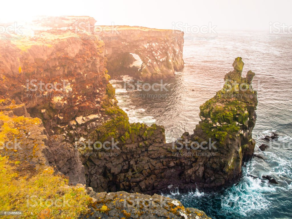 Londrangar, rock lava formation in the sea. Eroded basalt cliffs in the wild sea at coastline on Sneafellsnes peninsula, Iceland stock photo
