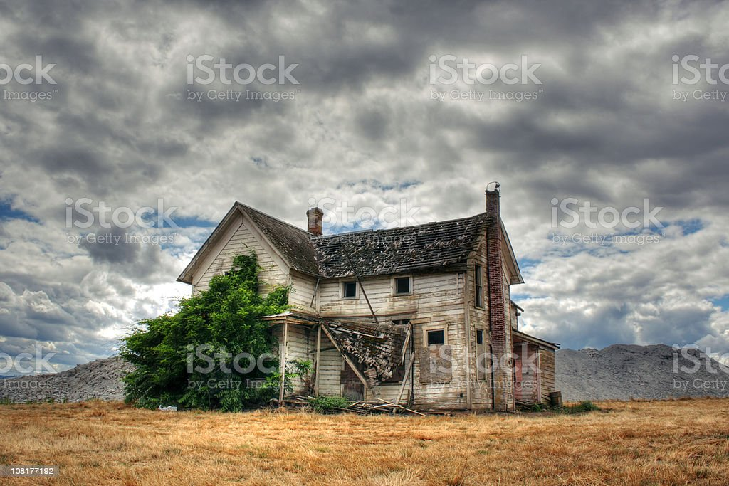 Lone, Abandoned and Derelict House in Field with Overcast Sky royalty-free stock photo