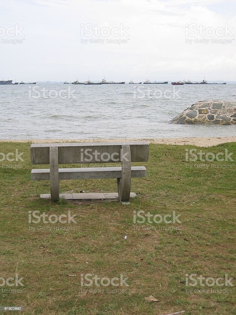 Lone bench facing sea royalty-free stock photo
