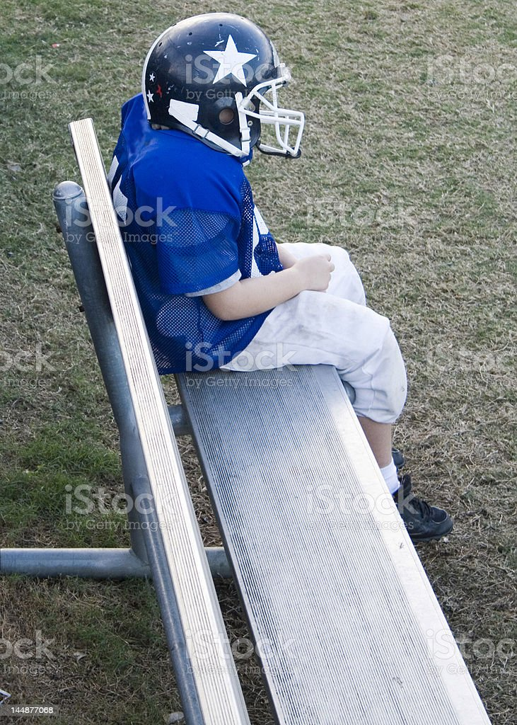 Lone benched youth football player. royalty-free stock photo