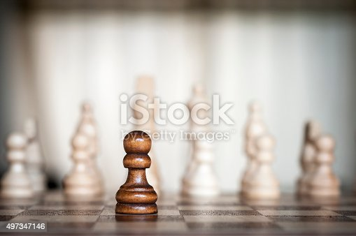 Lone Black Chess Pawn With Multiple White Chess Pieces In The Background