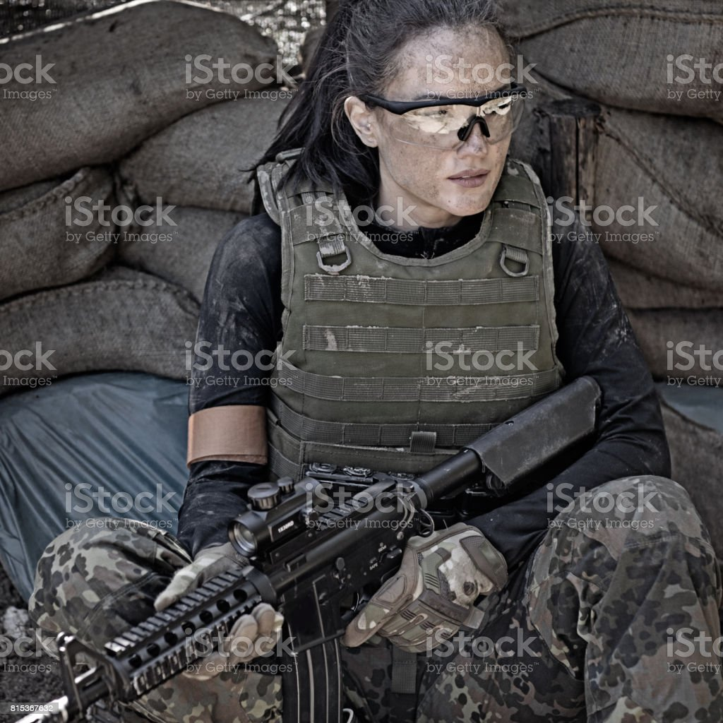 Lone brunette female soldier in outdoor setting stock photo