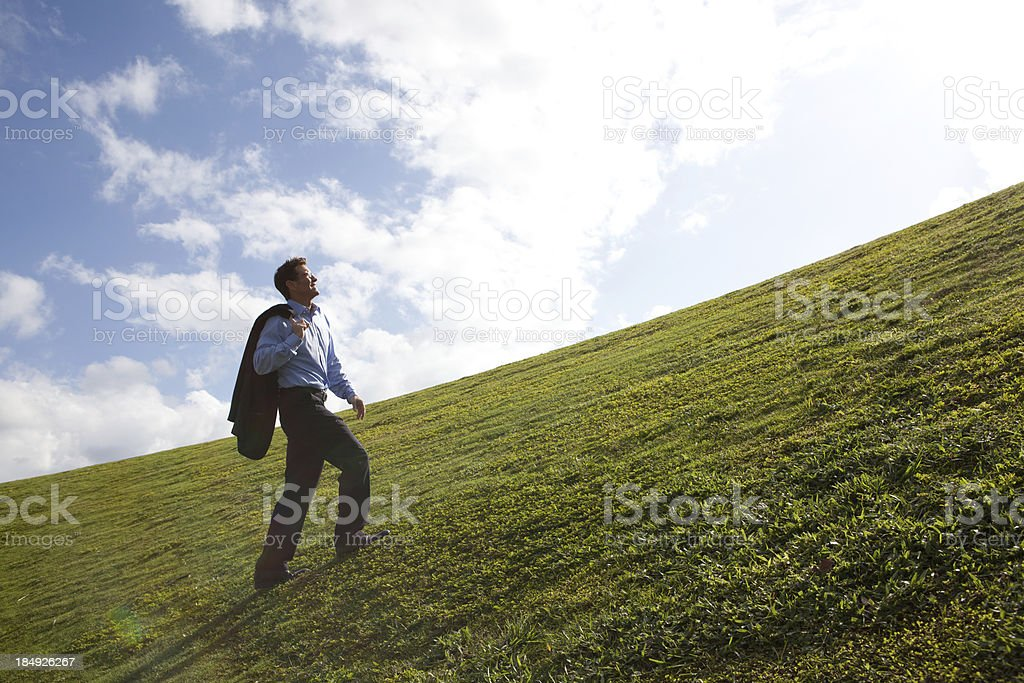 Lone business man walking up hill royalty-free stock photo