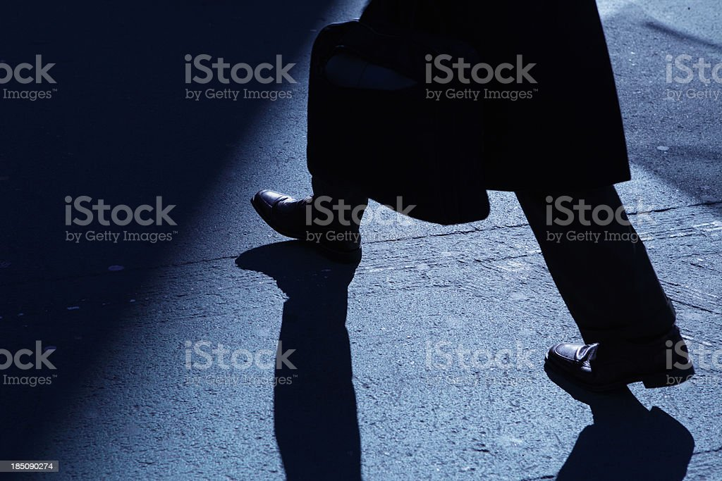 Lone businessman walking into blue night shadows royalty-free stock photo