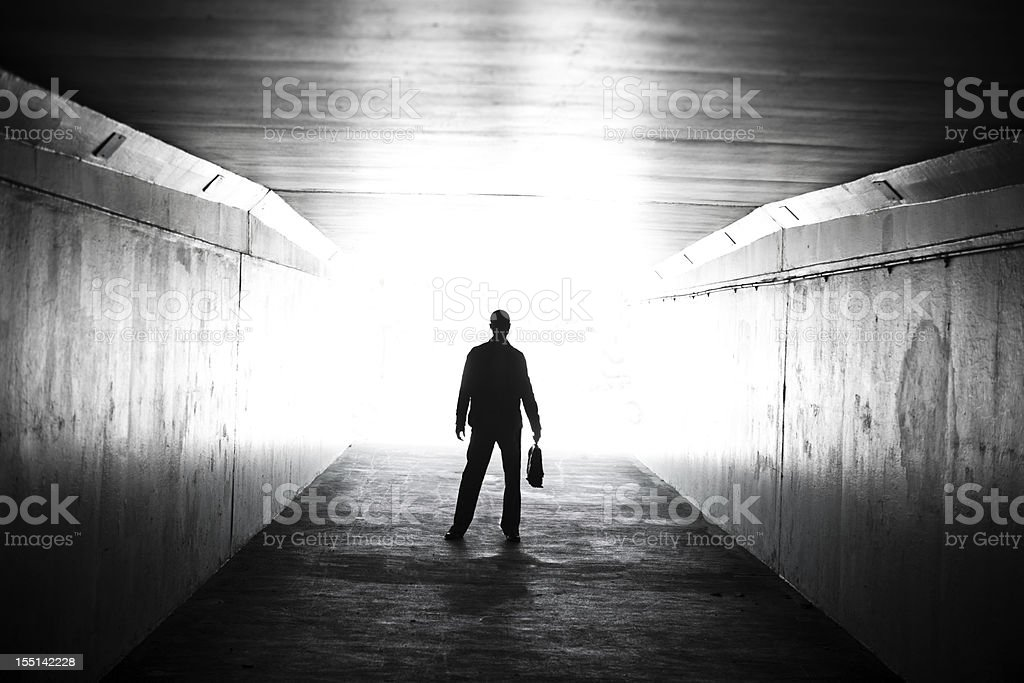 Lone businessman walking through tunnel with briefcase stock photo