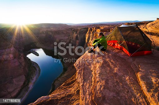 A woman overlooks the Colorado River from a campsite on the edge of Marble Canyon in northern Arizona. Sunstar is real.
