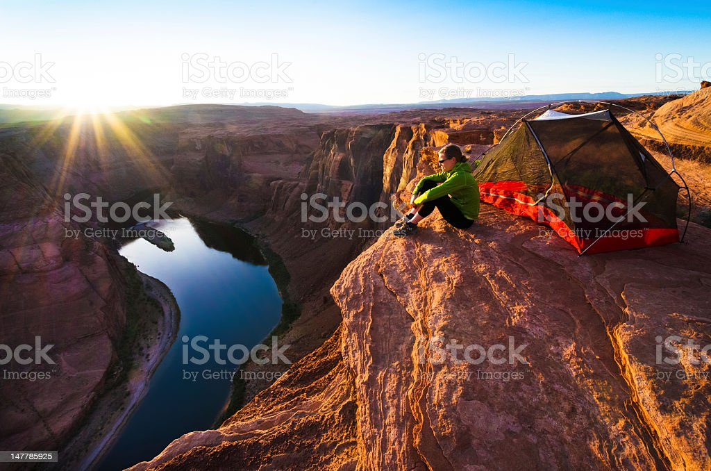 Lone camper sitting on top of mountain and edge of cliff stock photo