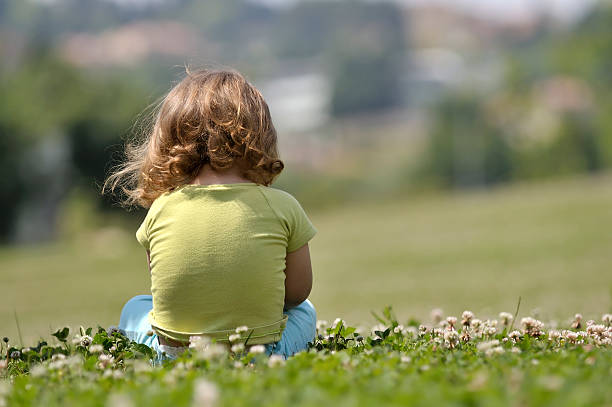 Lone child sitting in field of flowers stock photo