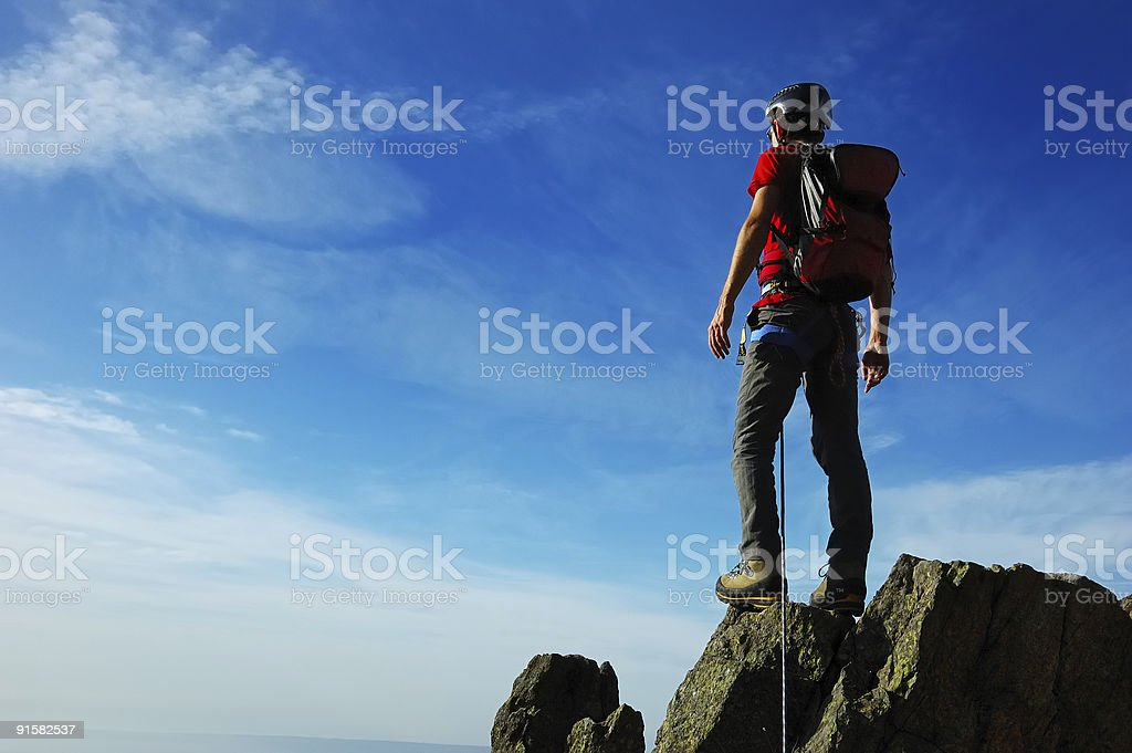 Lone climber reaching the peak of mountain overlooking sky royalty-free stock photo