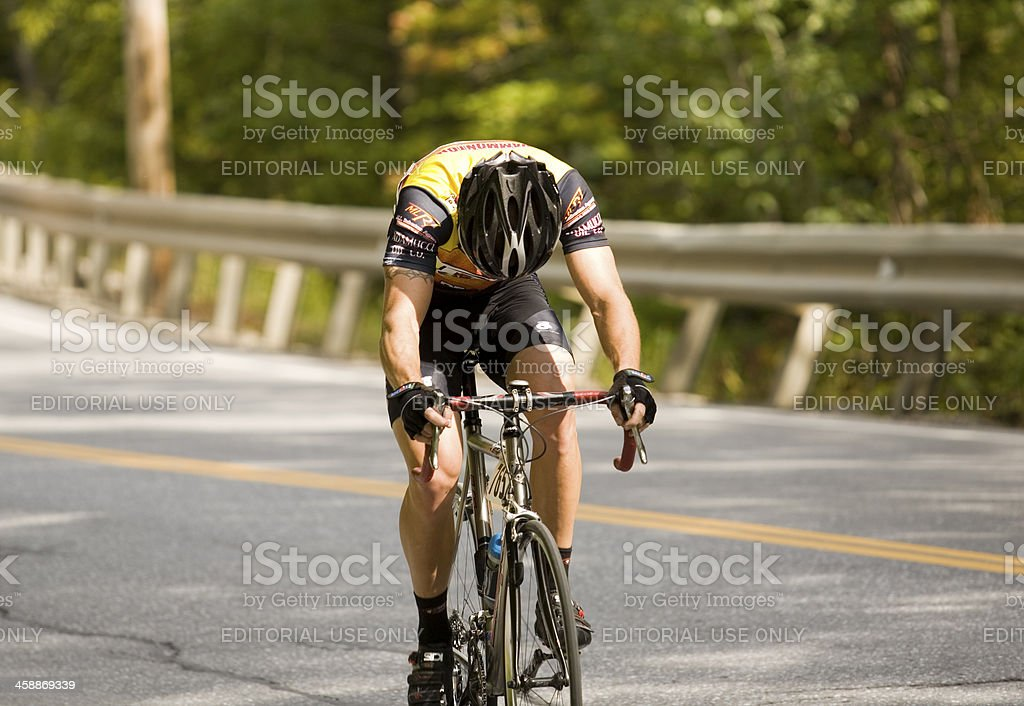 Lone Cyclist Struggles up a Steep Slope stock photo