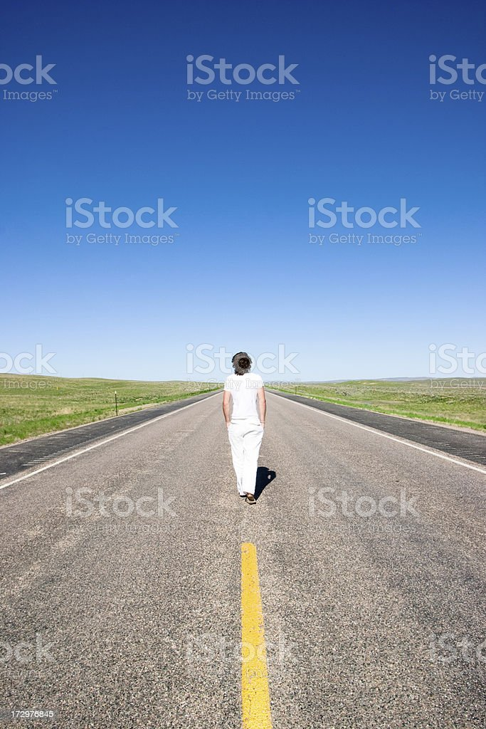Lone figure dressed all in white walking down a road royalty-free stock photo
