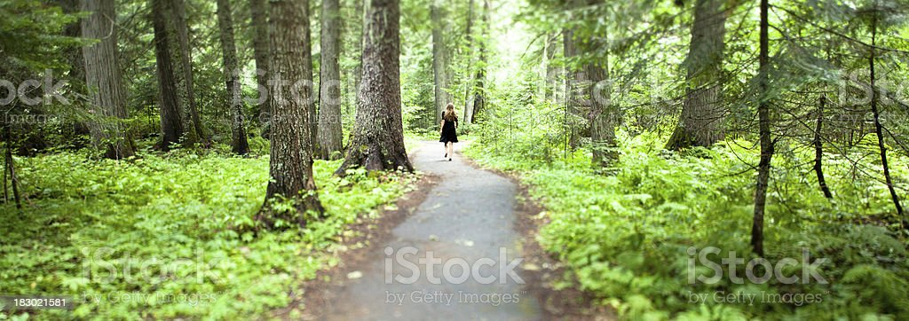 Lone figure in a black dress walking down forest path royalty-free stock photo