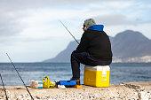 istock Lone fisherman fishing from Kalk Bay Harbour 1255411467