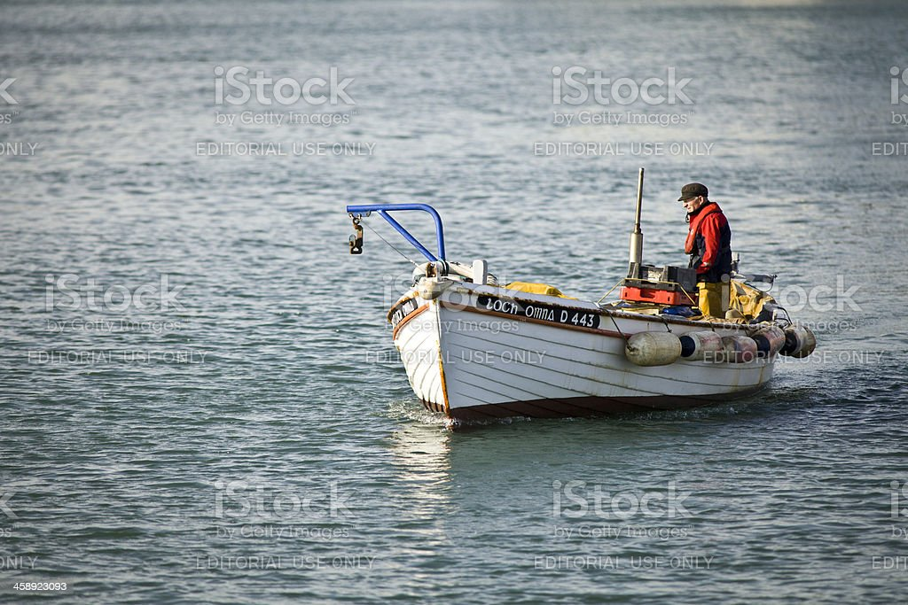 Lone fisherman heading out to sea in his boat stock photo
