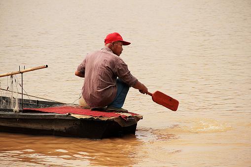Jiangxi, China - May 04, 2012: Colour photograph of a lone fisherman wearing a red hat, casting his net out on Zhangshui River in Ganzhou city in Jianggxi (China).