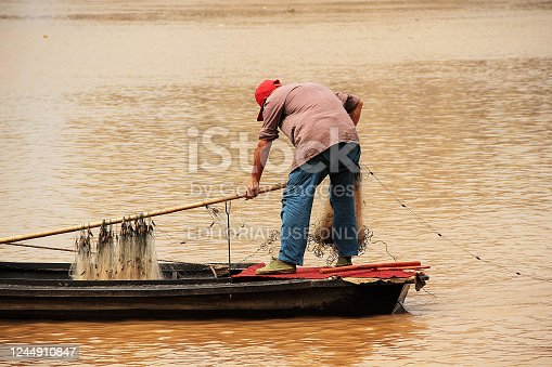 Jiangxi, China - May 04, 2012: Colour photograph of a lone fisherman wearing a red hat, casting his net out on Zhangshui River in Ganzhou city in Jianggxi (China).