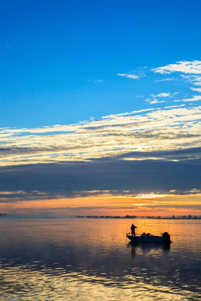 Lone Fisherman on the Lake at Dawn