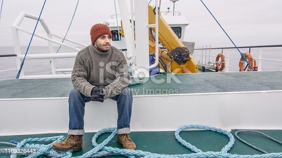Lone Fisherman Sitting on Bench at the Commercial Ship.