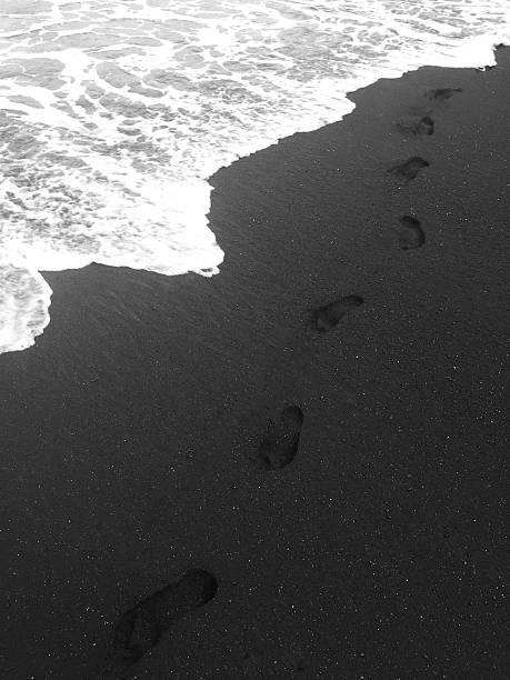 Lone footsteps on black sand beach Lone footsteps from a walk on a black sand beach - Maui, Hawaii black sand stock pictures, royalty-free photos & images