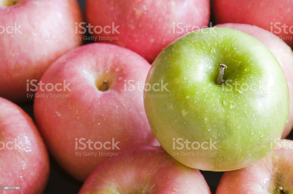 Lone green apple sitting on red apples. royalty-free stock photo