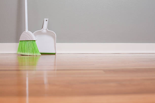 A lone green broom and dust pan Broom and dust pan on New Hardwood Flooring broom stock pictures, royalty-free photos & images