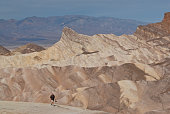 A lone hiker is strolling with his camera in hand near Zabriskie Point in Death Valley National Park, California, USA.