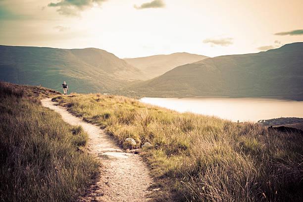 Lone hiker walking on Ben Lomond mountain stock photo