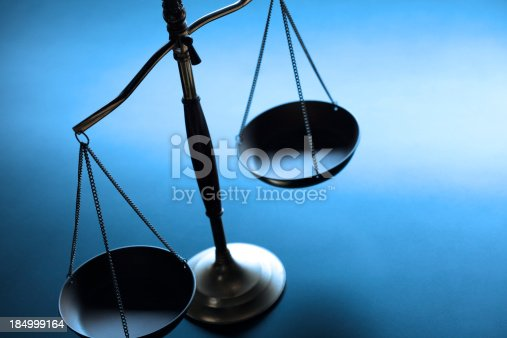 A justice scale on a simple blue background.  The scale is partially silhouetted as a strong backlight obscures some of the finer details.  Scale is place on left hand side of image leaving ample negative space for copy. Image can be flipped horizontal to accommodate alternative composition needs.