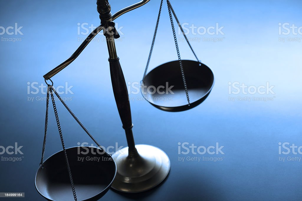 Lone justice scale on simple blue background stock photo