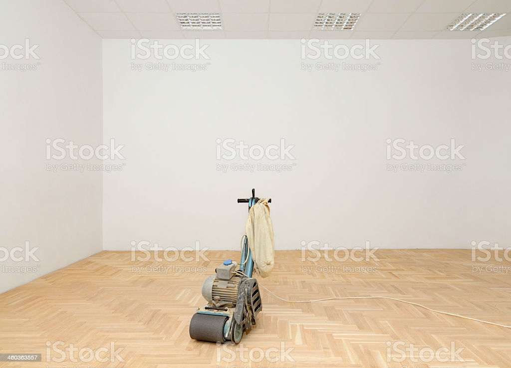 Lone machinery on wooden floors next to white walls in home stock photo
