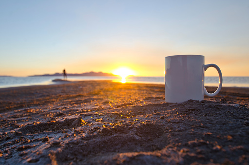 A view of a lone man and a solo blank white coffee mug on the shorelines of the great salt lake in the utah summer sun.