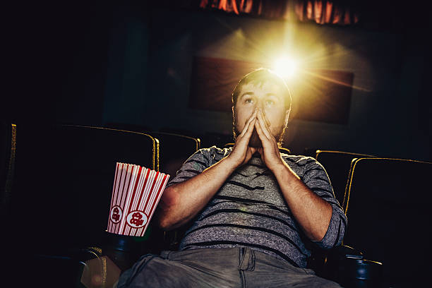Lone man at the movies Lone man in a movie theater critic stock pictures, royalty-free photos & images