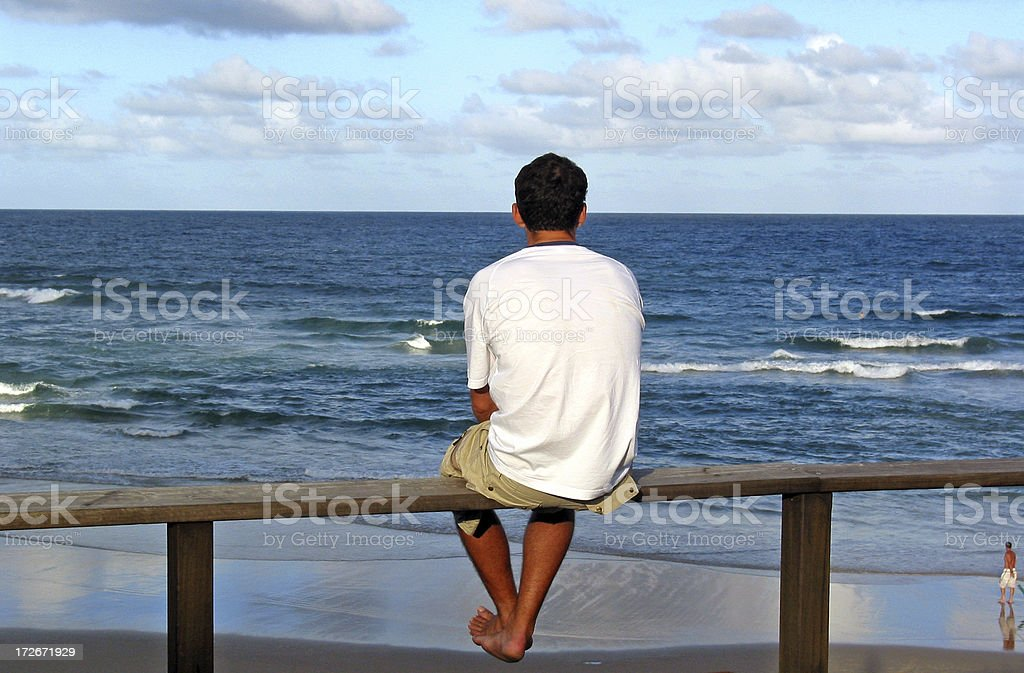 Lone man looking out to sea. stock photo