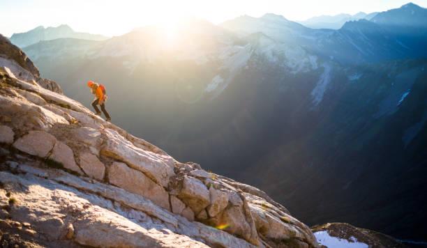 Lone man mountain climbing stock photo