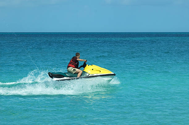 Lone man on a yellow jet ski in the ocean stock photo