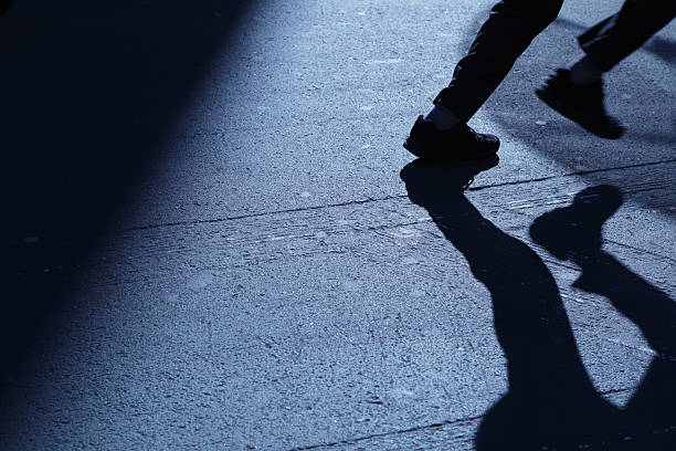 Lone man running away in blue night shadows stock photo