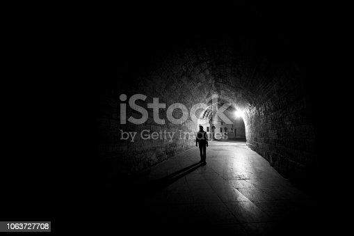 Lone man walking through tunnel