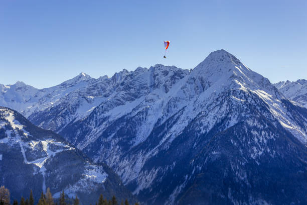 Lone paraglider above snow capped spring textured mountains stock photo