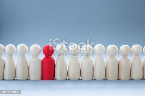 A row of human figures with a single individual standing out from the rest representing individuality and being different such as having a disease like coronavirus and infecting others or race, class, social differences